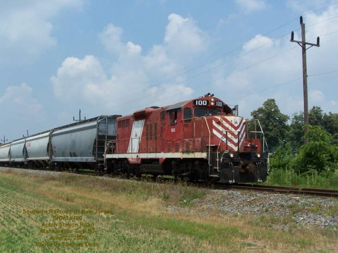 Southern Railroad Of New Jersey #100 leads a train in the farmland of Mannington Township, at the Acton Station Road crossing. Photo June 22, 2008.