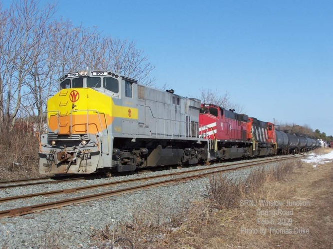 Three SRNJ widecabs along Spring Road at Winslow Junction on Feb 6, 2009 with a train of tank cars.